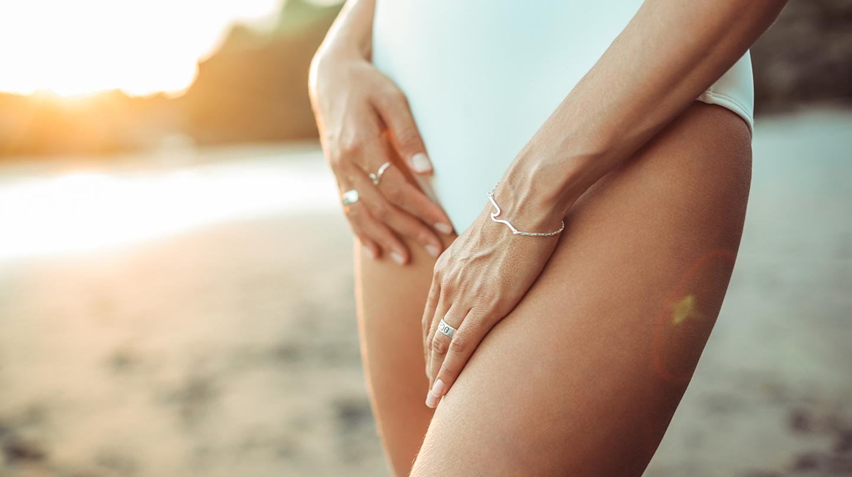 Blasenentzündung: Ausschnitt von Bauch und Beinen einer Frau im weißen Badeanzug am Strand.