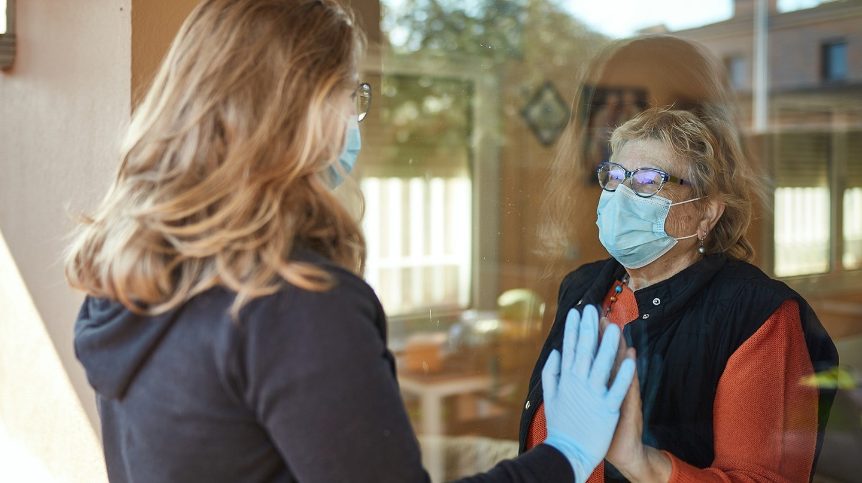 Seniorenheim: Eine ältere und eine jüngere Frau mit Einmalhandschuh und Mund-Nasen-Maske blicken sich durch eine Fensterscheibe an und halten eine Hand aneinander.