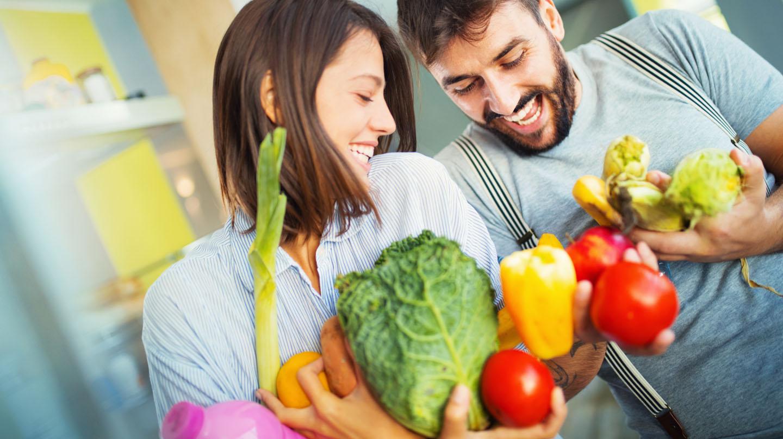 Junges Pärchen in der Küche mit Paprika, Tomaten, Porree und Kohlkopf in den Händen.