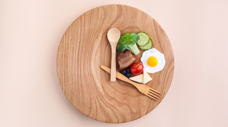 Intervallfasten: Löffel und Gabel sind auf Holzteller platziert wie die Zeiger einer Uhr. Dazwischen liegen Lebensmittel wie Gemüse und Ei.