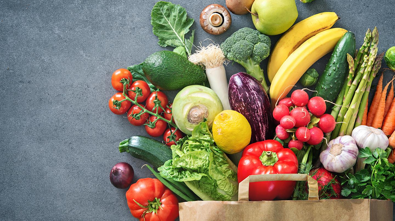 Vitamine und Mineralstoffe: Papiertüte mit frischem Obst und Gemüse.