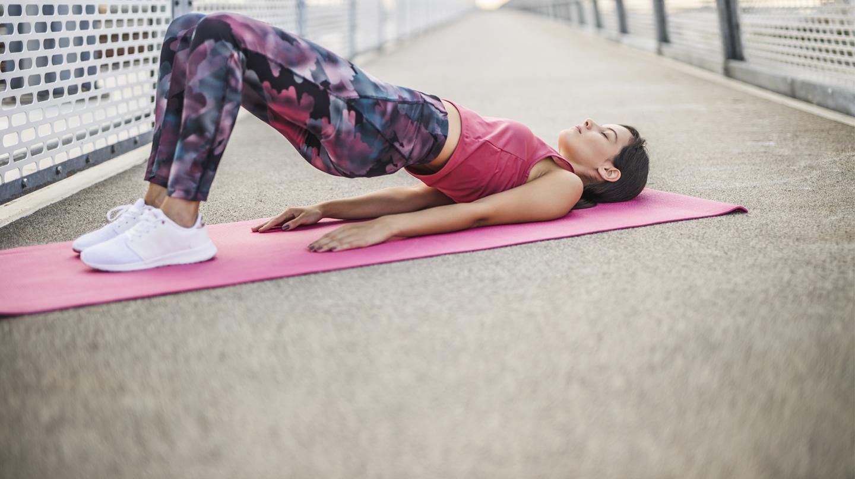 Inkontinenz: Jüngere Frau in Trainingskleidung liegt mit ausgestreckten Armen und angehobenem Gesäß auf pinkfarbener Trainingsmatte.